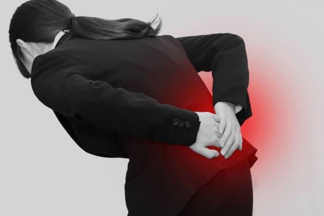 腰の痛みに苦しむ女性