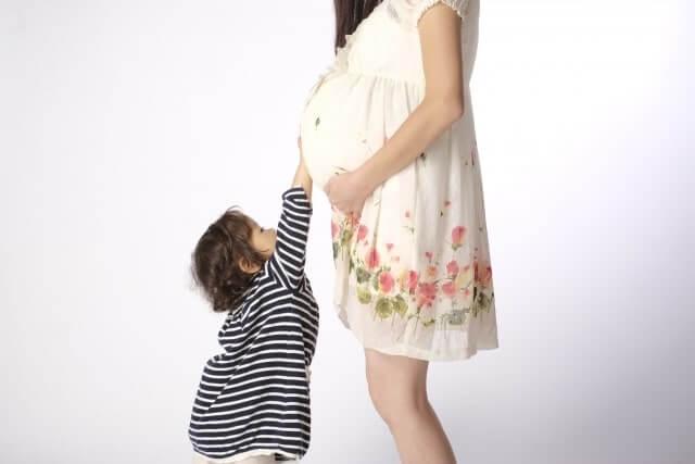 妊婦のおなかに手を当てるこども