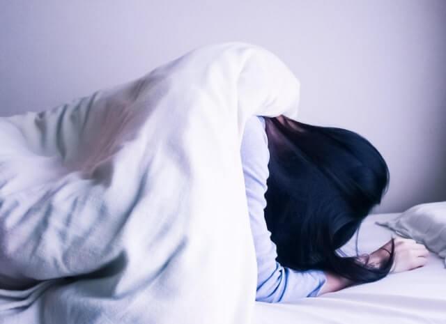 体調が悪く寝込む女性