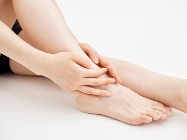 足首を触れる女性