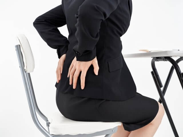 スーツ姿の女性が腰をおさえる