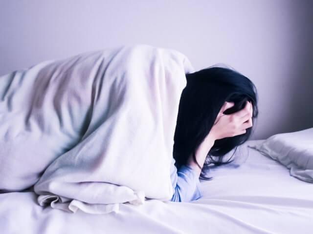 ベッドの中で頭を抱える女性