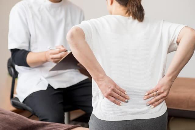 腰の痛みを相談する女性