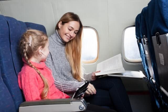 機内で子供本を読む女性